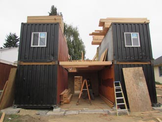 conatiners placed on slab house built around containers